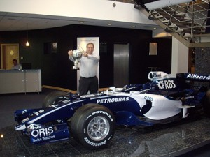 me holding the constructors\' trophy next to a Williams F1 car