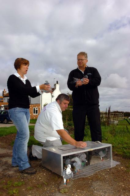 Michelle Brumfield and Trefor Davies release pigeons Rory and Tref with the assistance of Ray Knight from Unikon